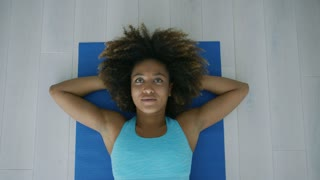 From above shot of young ethnic model in sportive top lying on back with hands under head and looking away in contemplation relaxing after workout.