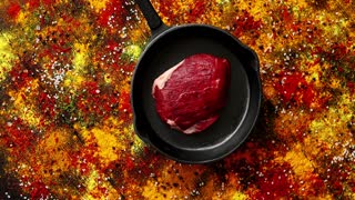 From above view of black pan with piece of raw meat placed on wooden background with spilt colorful spices