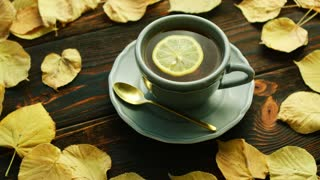 From above view of cup of hot tea with slice of lemon with saucer and spoon placed on wooden background and decorated with dry yellow leaves.