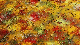 From above view of different colorful spices spilt all over wooden surface