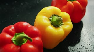From above view of fresh red and yellow peppers with green stems placed in line on black background covered with drops