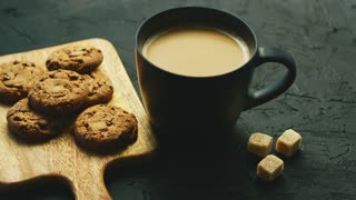 From above view of mug of hot coffee with biscuits laid on wooden cutting board and pieces of brown sugar on gray background