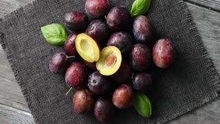 From above view of ripe shiny plums with green basil leaves composed on clean napkin on wooden table