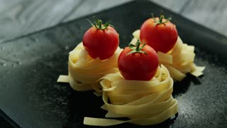 From above view of rolled tagliatelle with fresh tomatoes on top placed on gray table with drops on surface