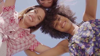 From below three young beautiful black and white women looking at camera and smiling on background of clear sky.