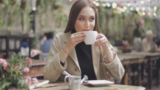 Gentle and stylish woman sitting in outside cafe at table with cup of coffee in hands and looking away