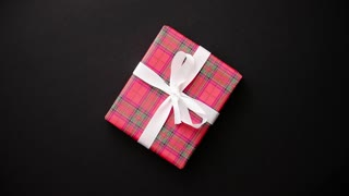 Gift box wrapped with red checkered pattern christmas paper with white bow on black table, top view