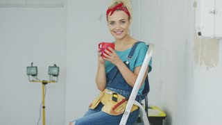 Gorgeous blond young female in jeans overalls and tool belt sitting on stepladder holding red mug with beverage and looking at camera smiling on background of unpainted wall .
