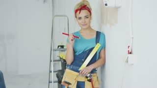 Gorgeous young blond female in jeans overalls and tool belt holding ruler and pencil leaning on shoulder against white plastered wall and smiling looking at camera .