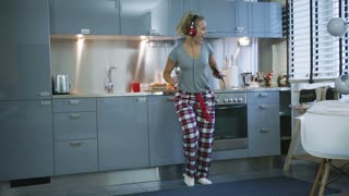 Gorgeous young woman in loungewear dancing and singing in spoon while listening to music in stylish kitchen.