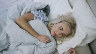 Gorgeous young woman with blonde hair lying in comfortable bed under warm blanket and peacefully sleeping.