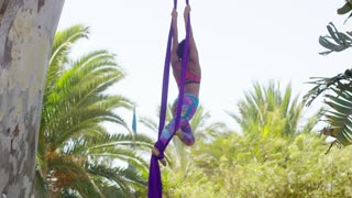 Graceful athletic young acrobatic dancer performing on two silk purple ribbons hanging midair in an elegant pose