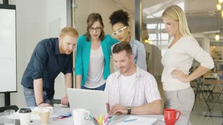 Group of multiethnic people in casual clothing standing at table with laptop and celebrating winning giving high five and looking excited.