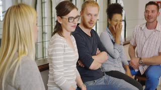 Group of people sitting in office, listening to their colleague and looking at her during break.