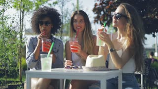Group of three young trendy women sitting at small table in outside cafe having refreshing drinks in hot summer day