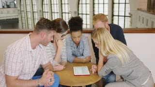 Group of young people in casual clothes sitting around table and looking through list of new ideas by using tablet.