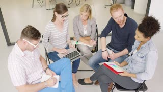 Group of young people in casual clothes sitting in office, looking at charts and discussing new work plans and strategies.