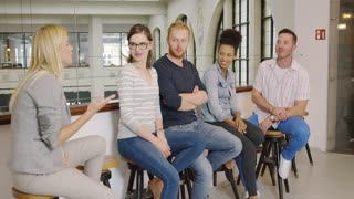 Group of young people in casual clothes sitting on bar stools during break and listening attentively to their colleague.