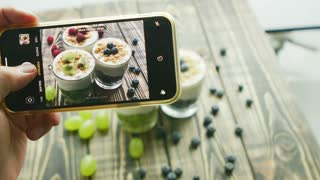 Hand of unrecognizable person using modern smartphone to take wonderful picture of amazing fruit desserts in cups on lumber table