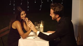 Handsome couple holds hands across dinner table in fancy restaurant at night with hanging lights