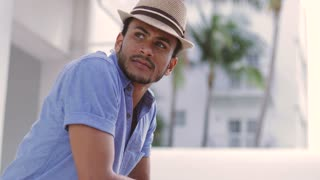 Handsome young ethnic man wearing hat standing and looking away on balcony on the street.