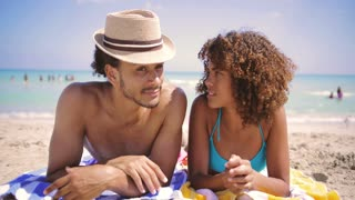Happy adult ethnic man and woman lying on sandy beach and looking at each other at the ocean.