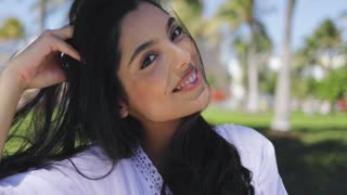 Headshot of charming ethnic girl with flying black hair wearing white dress and laughing at camera in tropical sunshine.