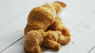 Heap of fresh crunchy croissants laid on white wooden background