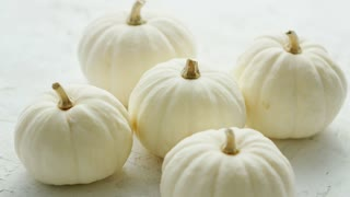 Heap of small white-colored pumpkins with dry stems on white background
