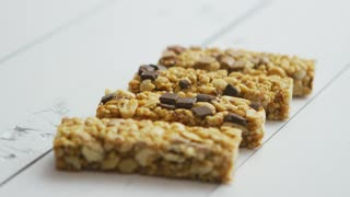 Homemade rustic granola bars with dried fruits on white wooden background