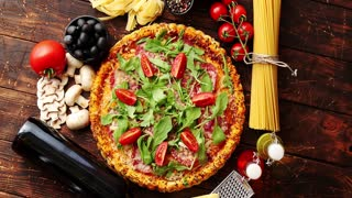 Italian food background with pizza, raw pasta, spices, herbs, wine, and vegetables on wooden table. Top view.