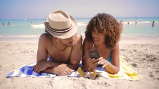 Joyful young romantic ethnic man and woman smiling and listening to music at the ocean.