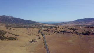 Landscape from drone of spacious desert terrain with roads and industrial plantations with windmills in bright sunlight, Andalucia, Spain.