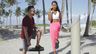 Laughing African-American girl in sportswear doing exercise under control of cheerful sportive man training on beach.