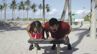 Laughing black woman and man in sportswear working out happily on sandy beach with gym in sunlight.
