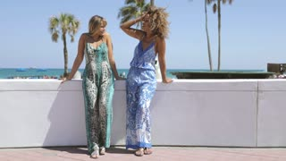 Laughing multiethnic women in stylish summer overalls standing on tropical waterfront in sunlight and chatting in fun.