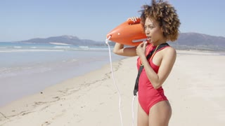 Lifeguard female wearing red swimsuit blowing a whistle holding rescue float. Tarifa beach. Provincia Cadiz. Spain.