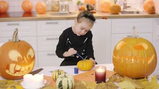 Little girl in cute Halloween costume standing near kitchen table and painting small orange pumpkin with gouache.