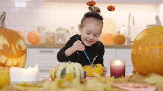 Little happy-looking girl in cute Halloween costume standing near kitchen table and painting small orange pumpkin with gouache.