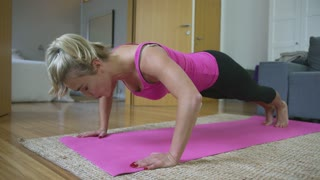 Lovely blonde woman in pink tank top doing push-ups while training on stretching mat in living room.
