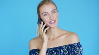 Lovely young lady with ponytail smiling and having smartphone conversation while standing on bright blue background