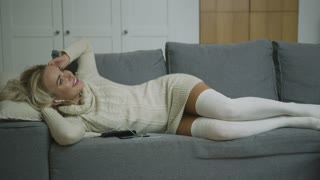 Lovely young woman in white dress and stockings listening to good music and smiling white lying on comfortable sofa.