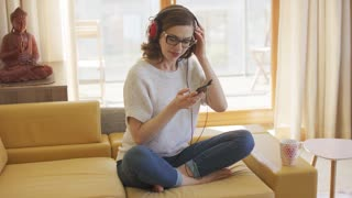 Lovely young woman smiling and choosing song on smartphone while listening to favourite music on sofa in stylish living room.