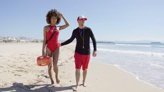 Male and female lifeguards pointing into distance on beach. Tarifa beach. Provincia Cadiz. Spain.