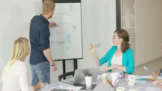 Man drawing simple graphic on board and presenting new information on project for coworkers at table in office.
