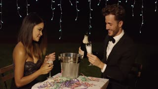 Man fills his glass with champagne to toast with his beautiful date at night time celebration