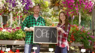 Man gesturing thumb up and woman pointing at open sign at blackboard standing and looking at camera together in the garden.