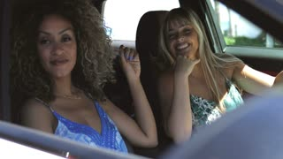 Multiethnic laughing women sitting in car and having fun looking in window and chatting in sunlight.