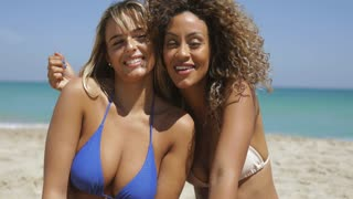 Multiethnic women in swimwear sitting on sandy tropical coastline of ocean and waving with hands at camera in bright sunshine.