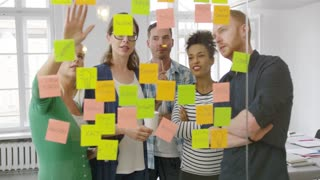 Multiracial group of people standing behind glass wall in office and watching at bright stickers on it brainstorming on new ideas.
